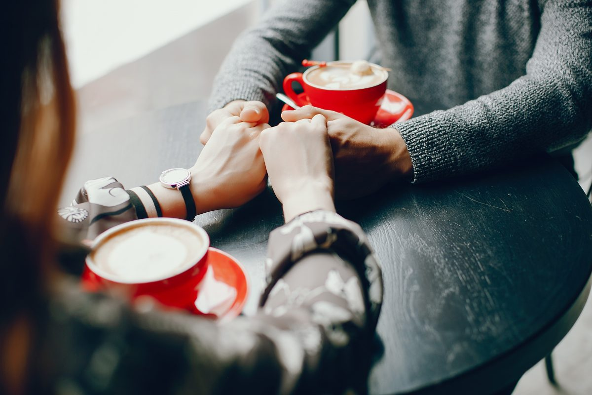 Beautiful couple sitting in a cafe. Cute girl in a shirt. Man in a gray sweater. Couple drinking a coffee