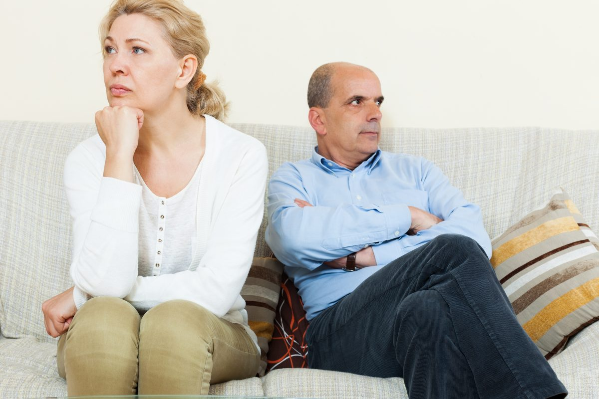 Sad  couple after quarrel in room at home